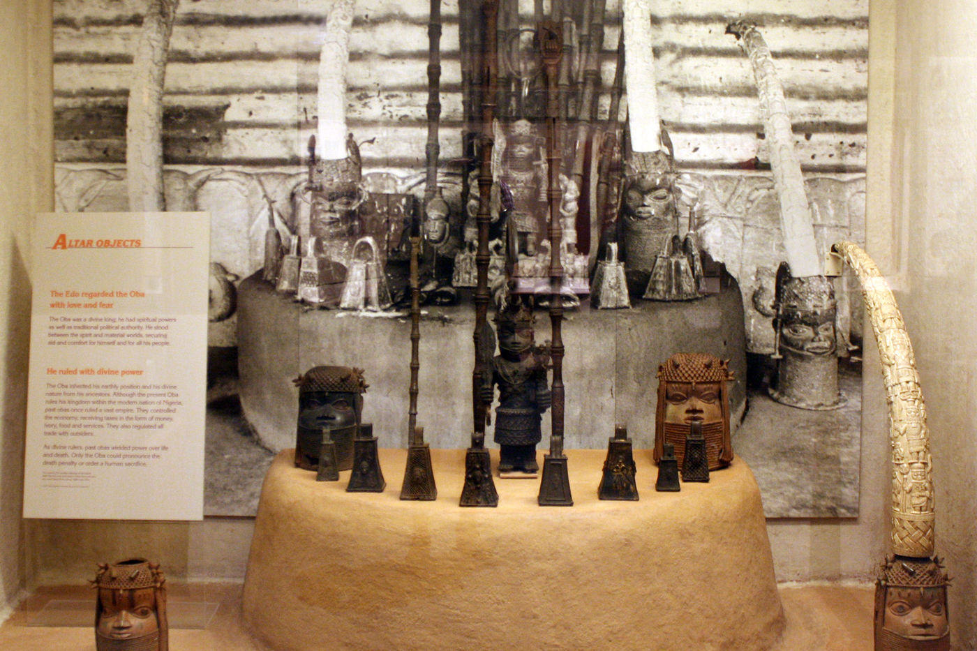 "A museum display with a sign that reads ""altar objects."" An array of carved figure, mostly human figures, is displayed on top of a small platform. A carved ivory tusk is seen on the right. Behind the display is a black-and-white photograph showing these and other objects arranged in a similar fashion."