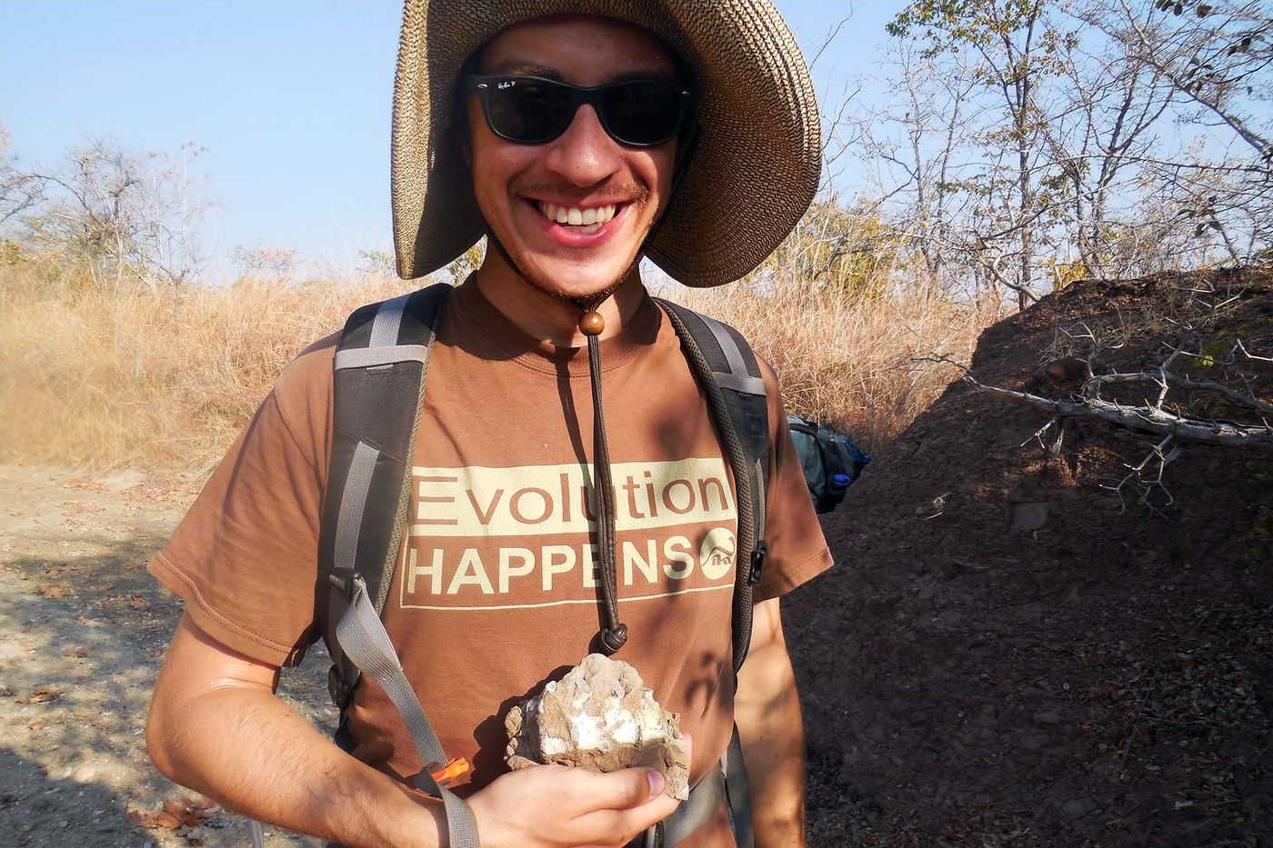 """A smiling man wearing a hat, sunglass, and a shirt that reads """"Evolution happens"""" holds a chunk of fossilized bone in his hand. Tall, dry grass and a mound of rock and dirt are visible in the background."""