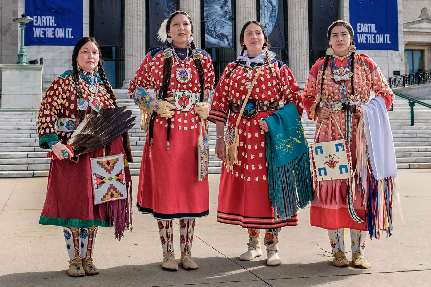 Four women dressed in Apsáalooke attire stand in front of the Field Museum.