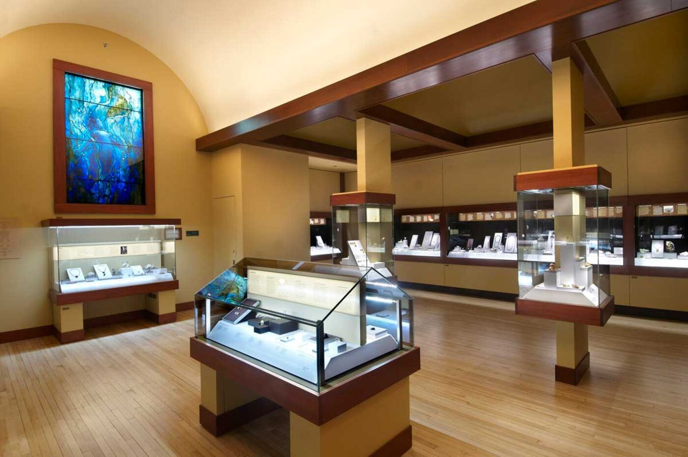The Grainger Hall of Gems gallery at the Field Museum, including glass display cases and a blue stained glass window.