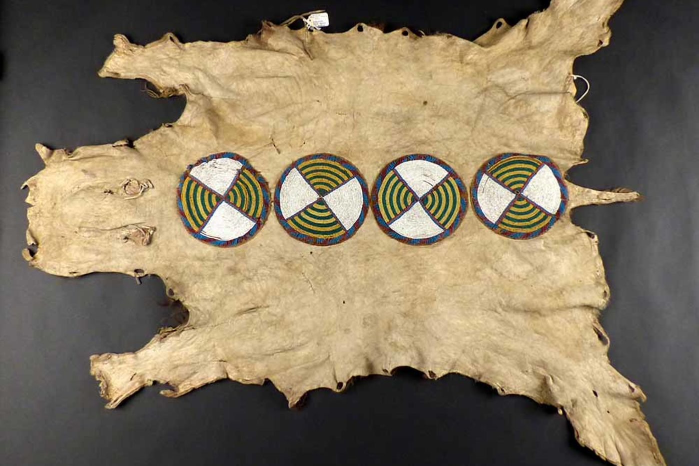 An animal hide painted with four circles containing a striped design
