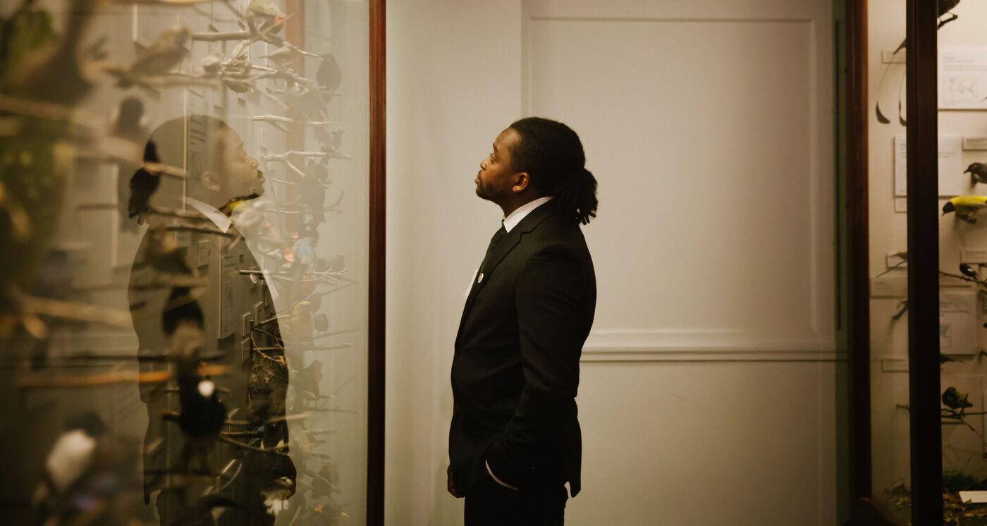 A man wearing a black suit stands looking into a exhibition display case.