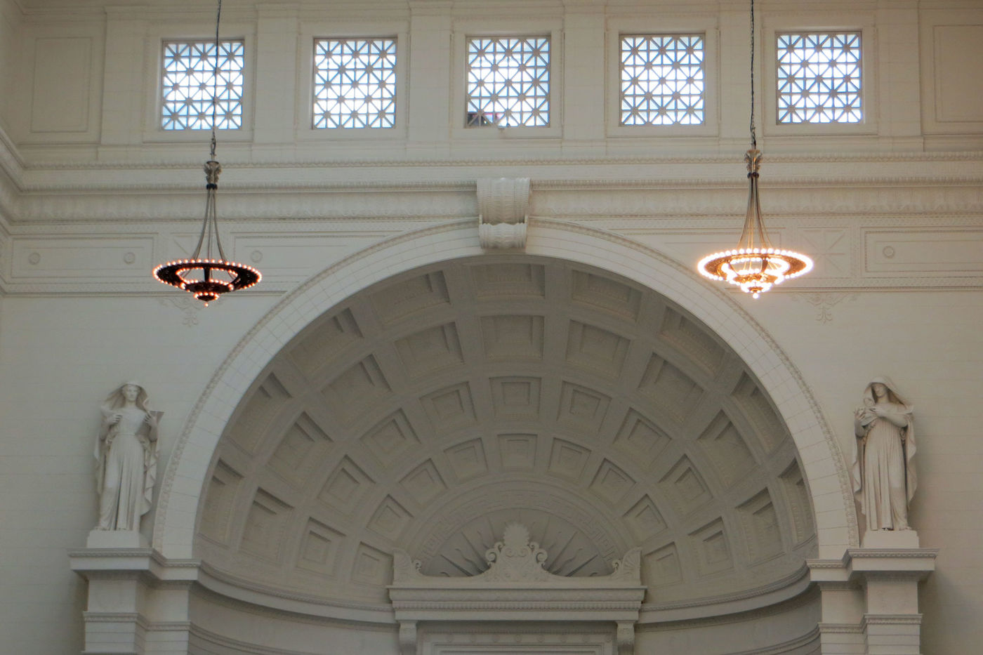 Two decorative chandeliers hang from the ceiling in a classical-style hall. The one on the left has dim, orange-hued light bulbs and the one on the right with much brighter, whiter light bulbs. Behind the chandeliers is an alcove with two sculptures of female figures standing on columns on either side.