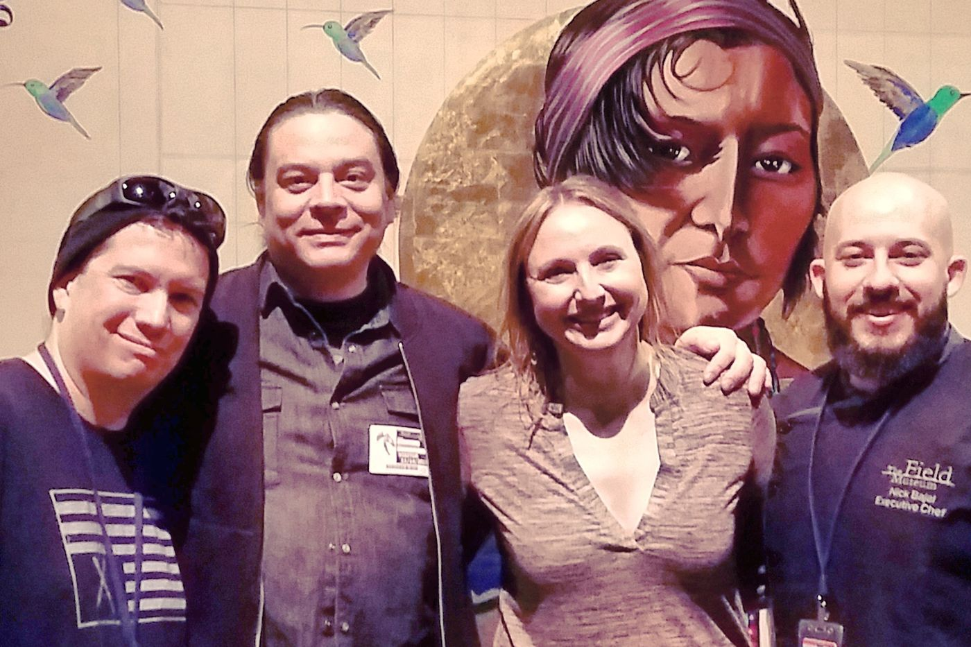 Four people, three men and a woman, smiling at the camera in front of a large mural with a woman's face and hummingbirds.