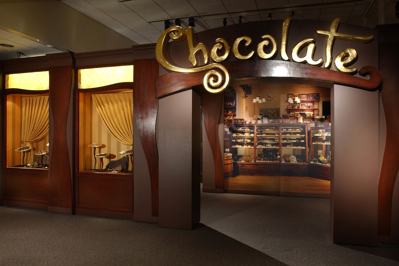 "Exhibition title ""Chocolate"" displayed over arched entranceway to exhibition. Through archway, a life-size image of a store chocolate display is visible."