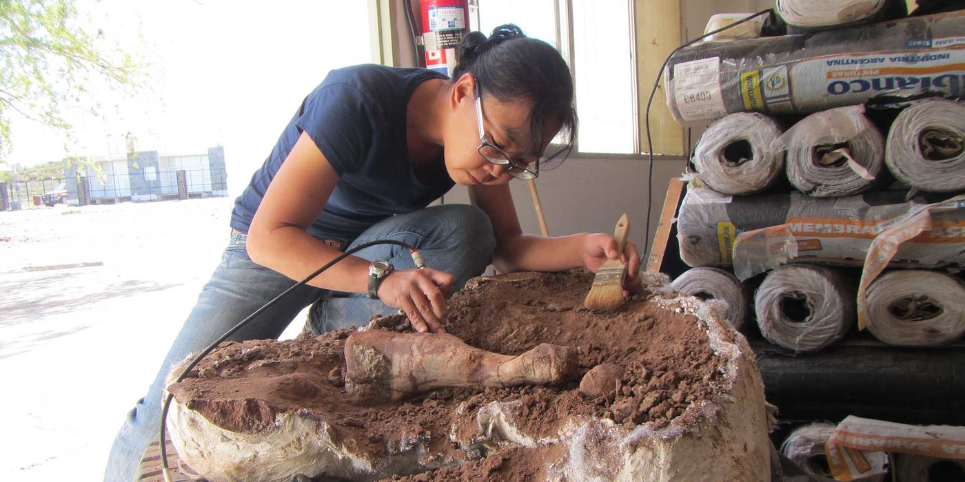 A woman holding an electric hand tool and a painter's brush, leaning over a large mass of dirt with bones protruding from it