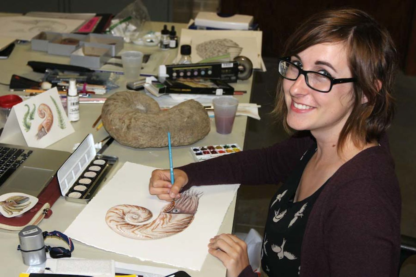 A woman sitting at a desk with art supplies, holding a pencil in hand and drawing a nautilus
