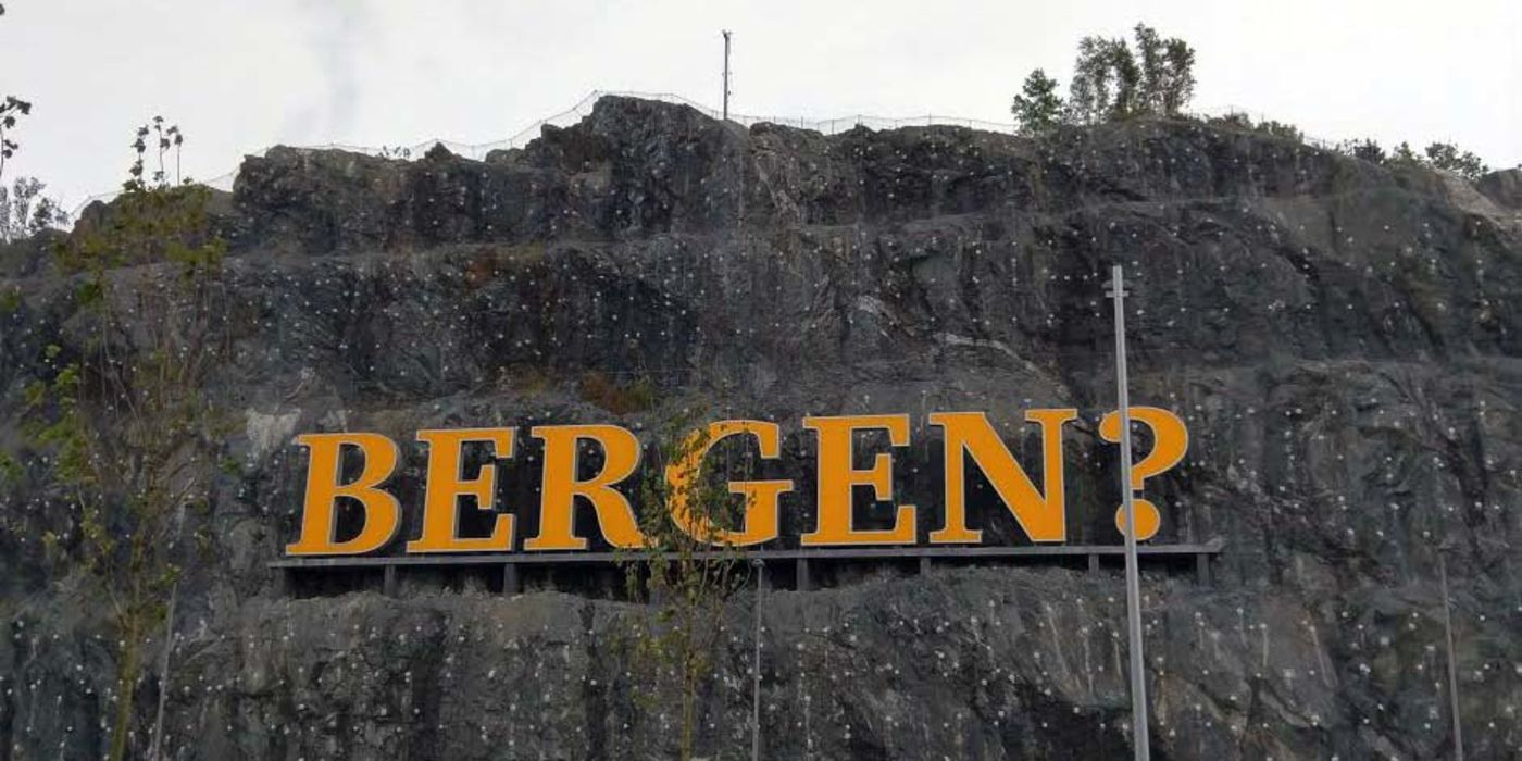 "A rock face with the word ""Bergen?"" affixed to it"