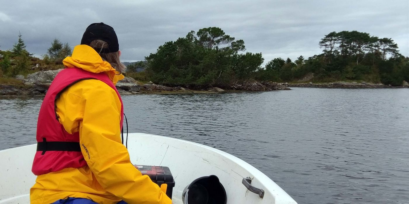 A woman wearing a yellow jacket and red life vest looking forward off the bow of a boat toward rocky shoreline.