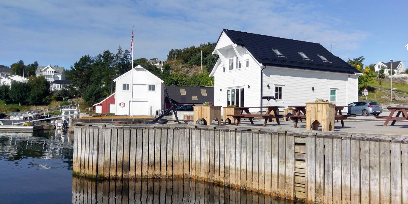 White buildings on a wooden dock overlooking the water