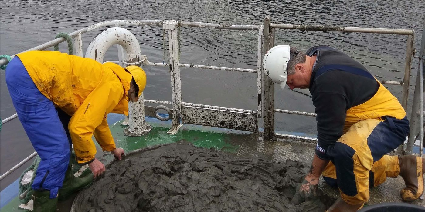 Two people wearing hard hats on a boat, leaning over and examining mud on the deck