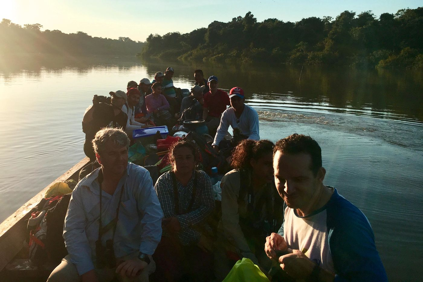 A group of people in a narrow, wooden boat on a wide river with trees lining both sides. The sun is very bright in the upper left corner.
