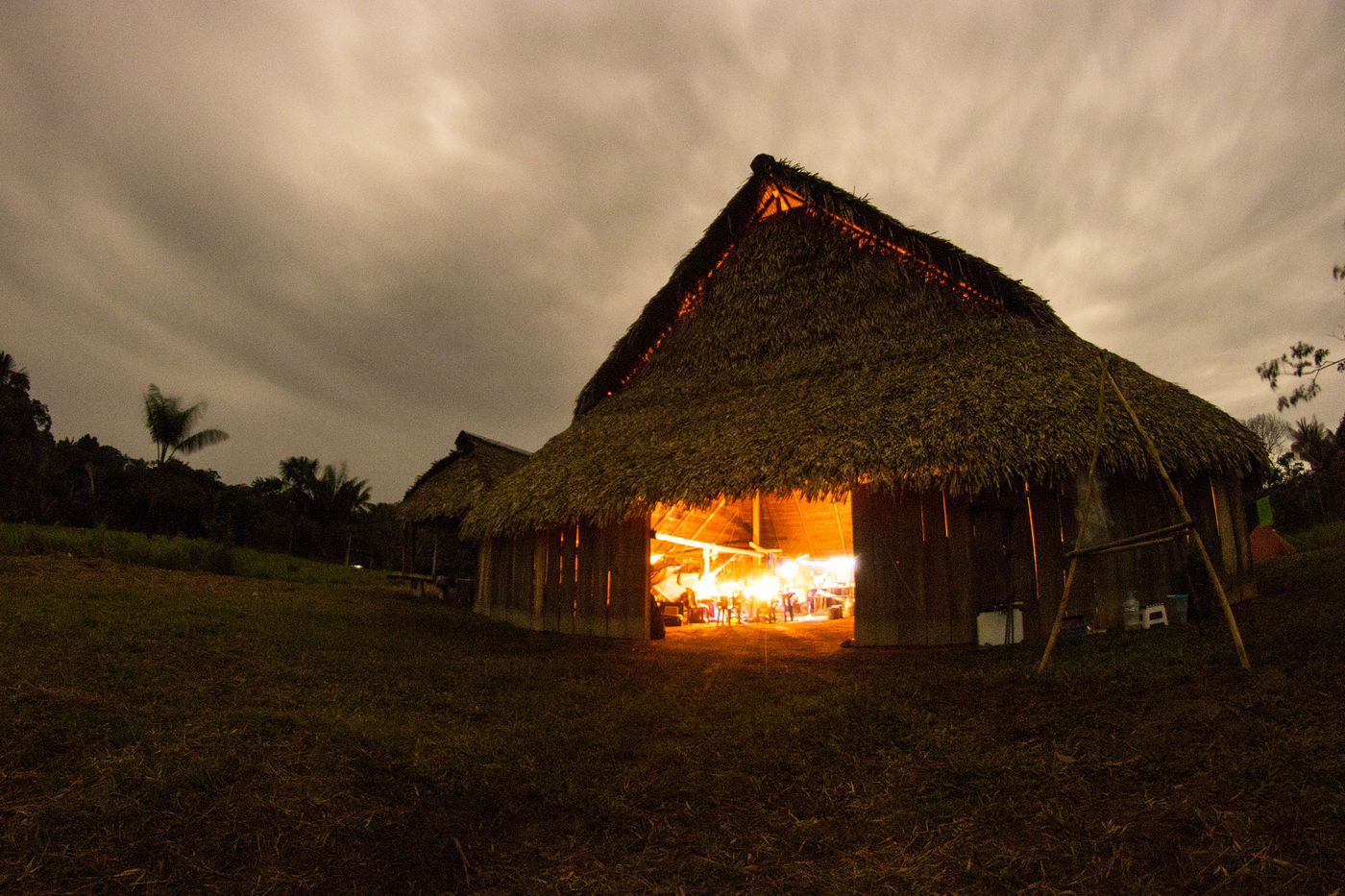 A wooden building with pointed thatched roof at nighttime. The warm, orange glow of candlelight is visible inside the building, through its wide-open front doors. There are palm trees behind the building.