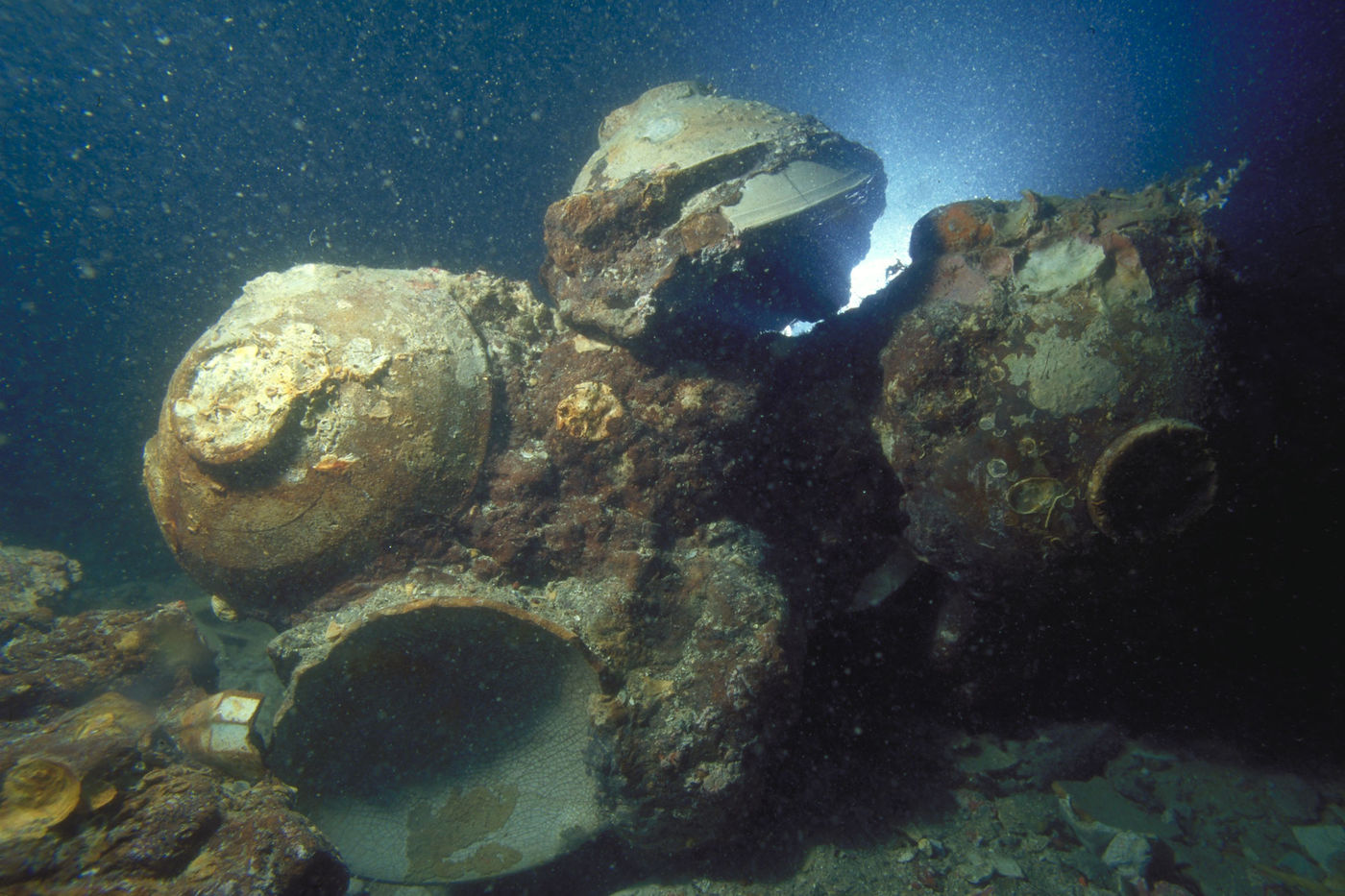 Several ceramic bowls rest on the seafloor, stuck together along with corroded iron and remnants of sea life.