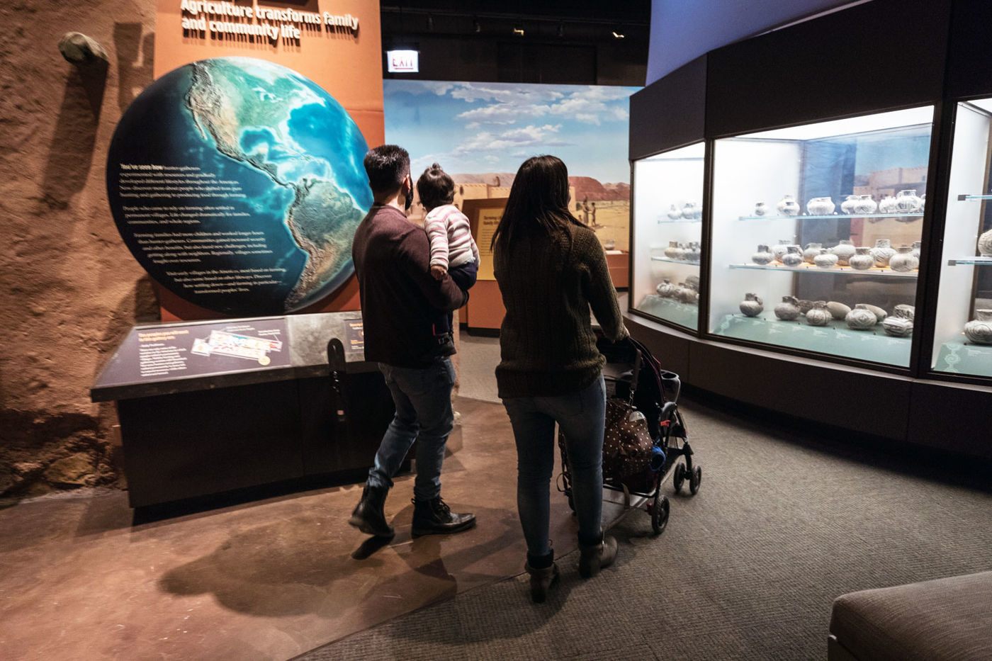 Two adults and a small child walk through the Ancient Americas exhibition. A map of the globe is on the wall to the left, and many pots are in a display case to the right.