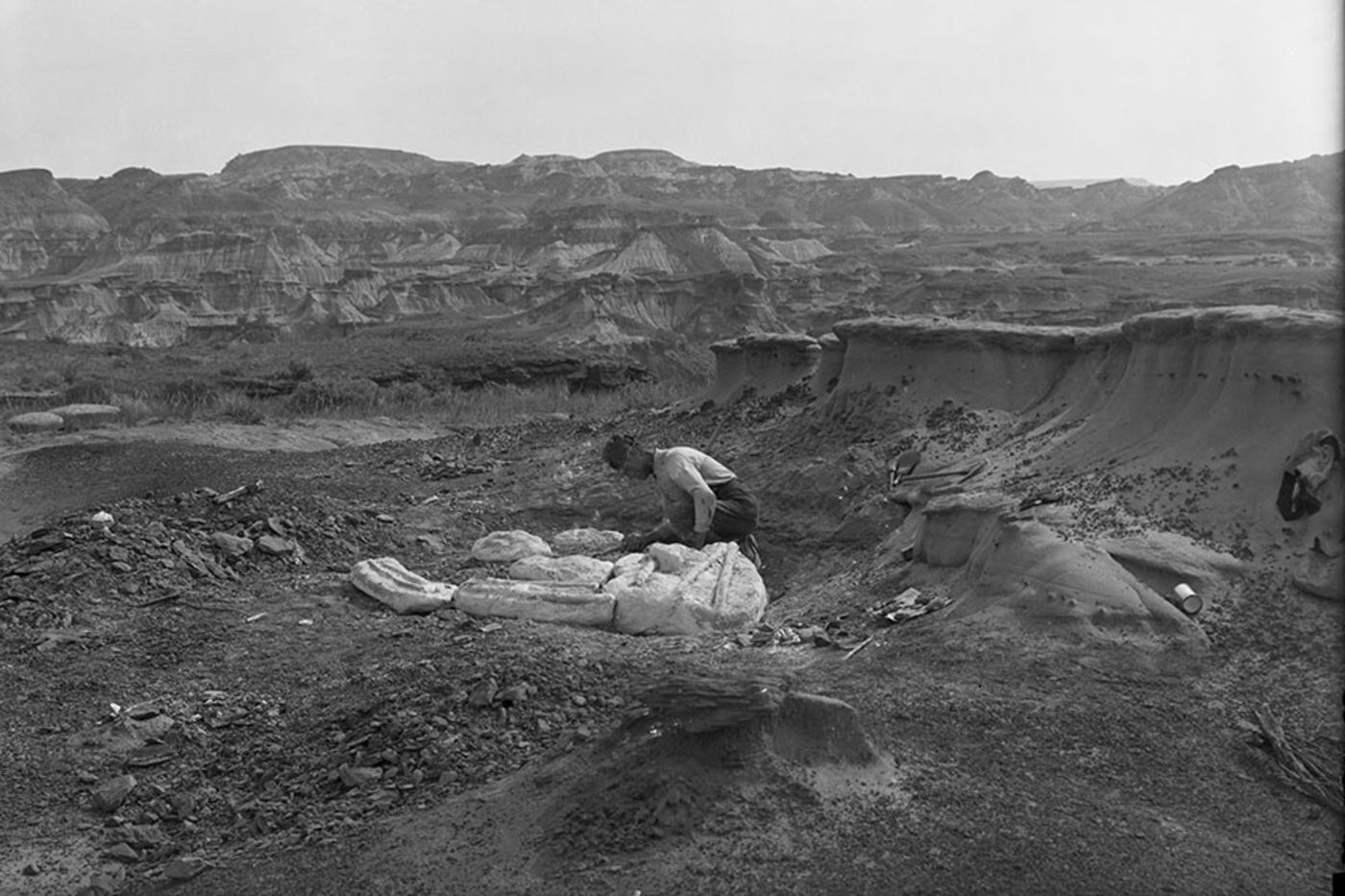 Black-and-white photo of a man in a rocky ditch, leaning over several large bundles covered in white plaster. There are mountains in the background.