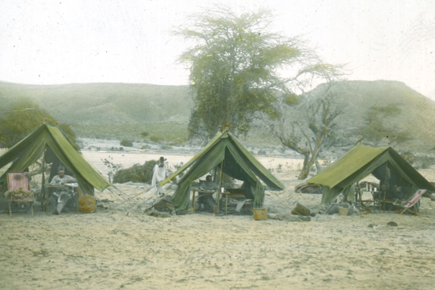 A colored photograph with black border, showing three tents in a row. The foreground is sandy, and the background has a few sparse trees and mountains.