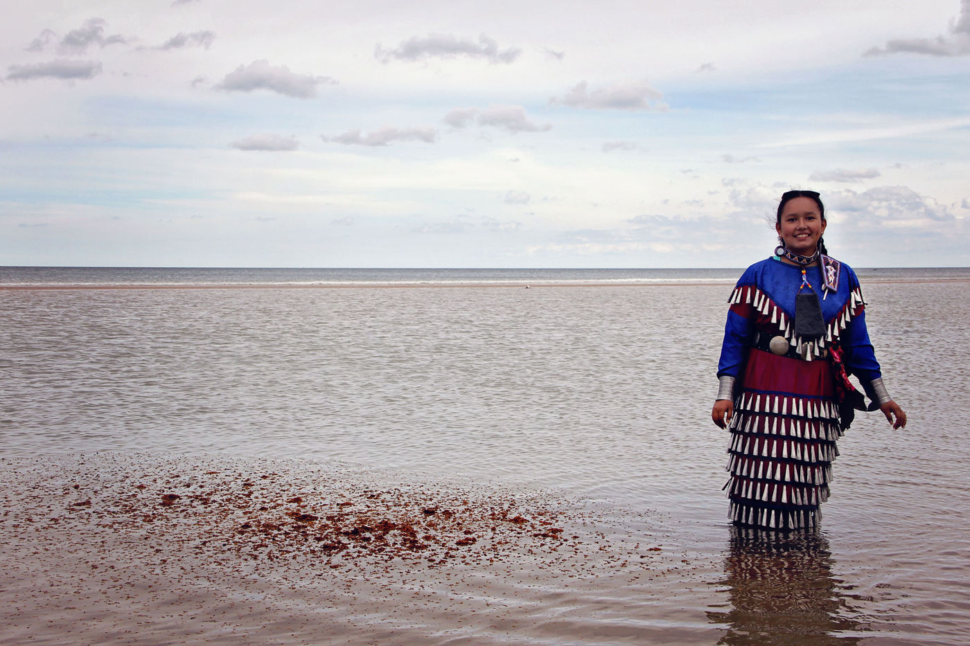 A young woman wearing blue and red ceremonial attire stands in shallow water. A red powdery substance floats on the surface of the water to her left. In the background, the sky is slightly overcast with some blue sky.