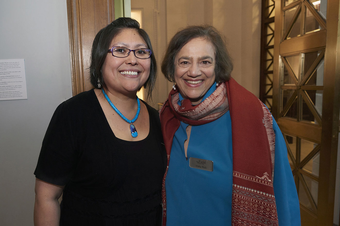 Two women stand next to each other and smile at the camera. One wears black with a blue necklace and glasses, and the other wears blue with a red scarf. An ornate brass door is visible behind them.