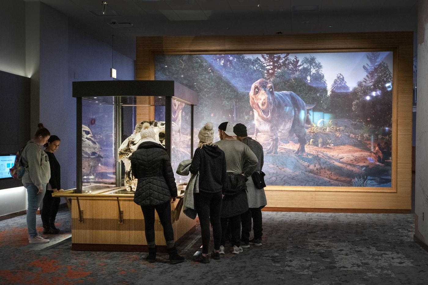 A group of people stand around a display case with a dinosaur skull in it. Behind them, a large mural depicts a T. rex walking through a forested landscape. Its mouth is slightly open and its bright green eyes seem to be looking right at you.