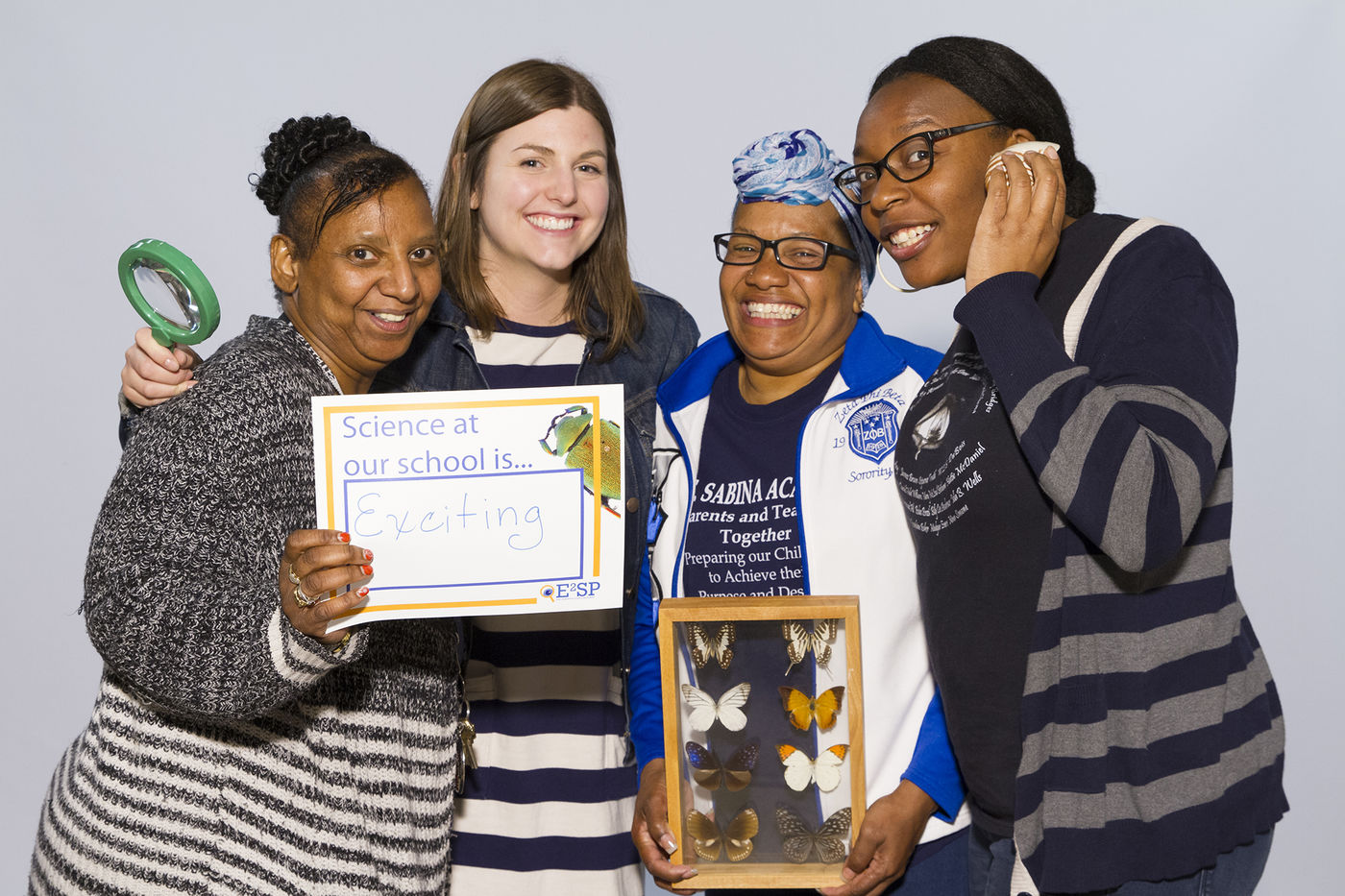 """Four Early Elementary Science Partnership (E2SP) educators pose for a photo. One holds a sign that reads """"Science at our school is exciting. Two others hold a magnifying glass and a glass case of butterflies. The other smiles while holding her hand lightly up to her face."""