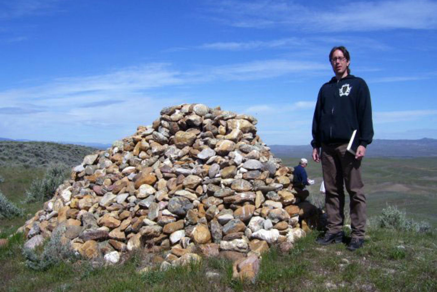 A man stands next to a stacked stone structure with a wide expanse of plains in the background.