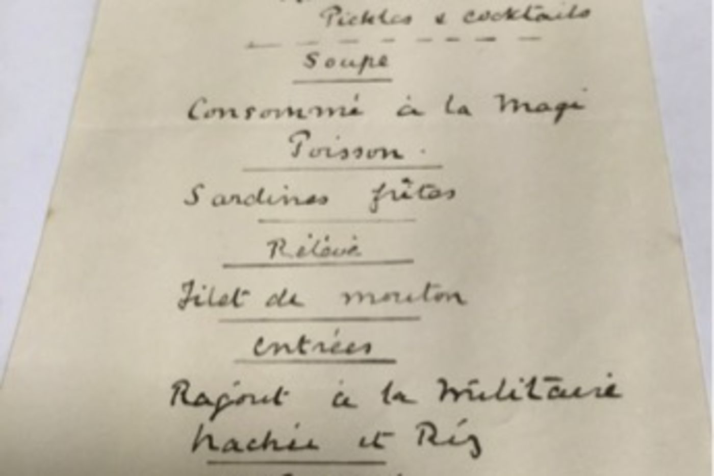 A piece of paper with a handwritten menu in French and a drawing of two flags at the top.