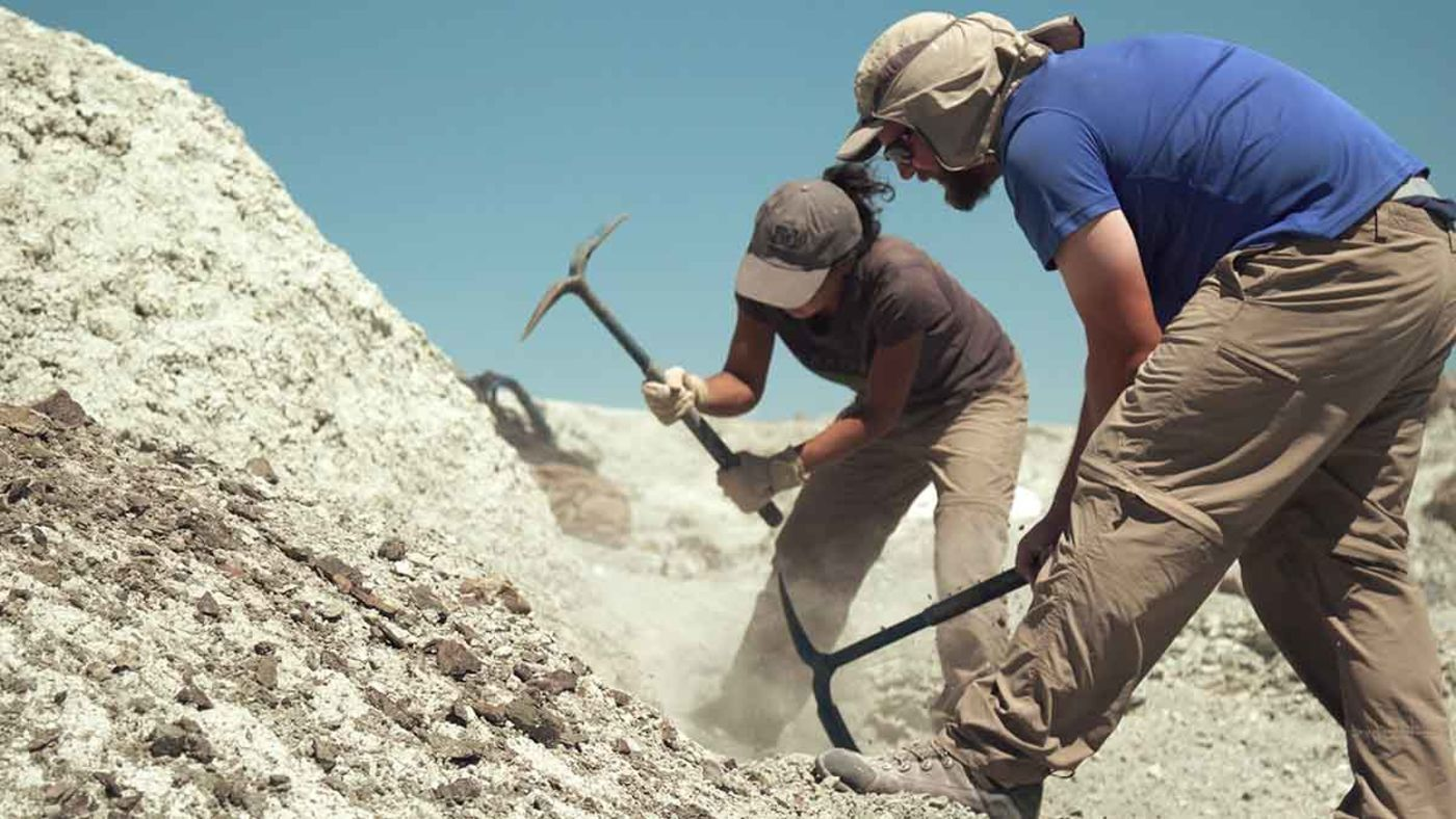 A man and woman with pickaxes digging in a rocky, dusty hill