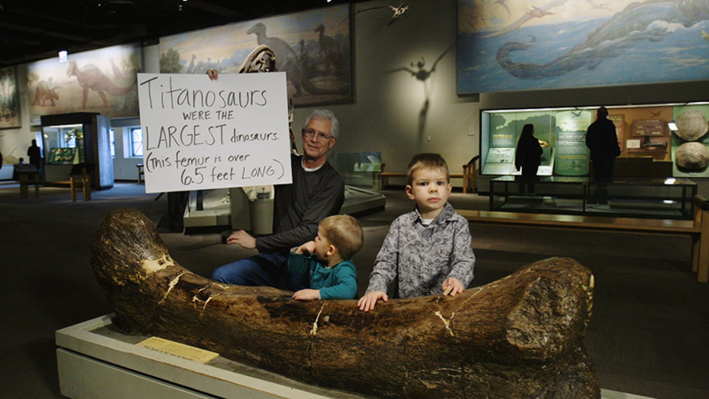 A man holding a handwritten sign, alongside two young boys, all behind a large dinosaur leg bone