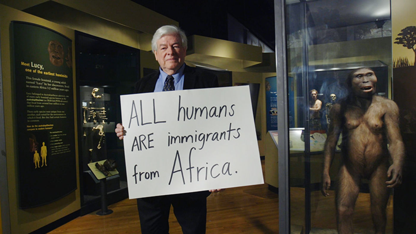 Man holding a handwritten sign, standing next to a figure of an early human relative.