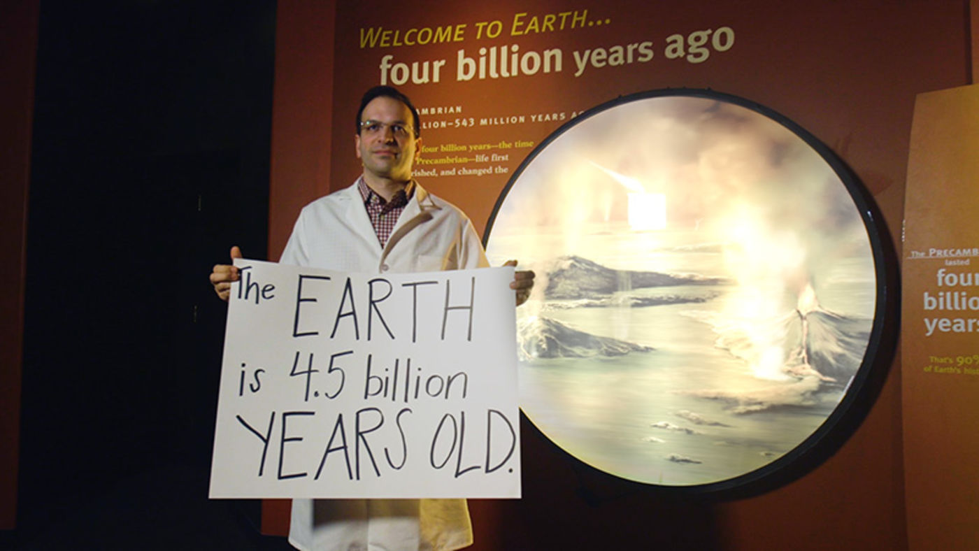 A man in a white lab coat holding a handwritten sign and standing in front of a museum exhibit showing volcanoes erupting.