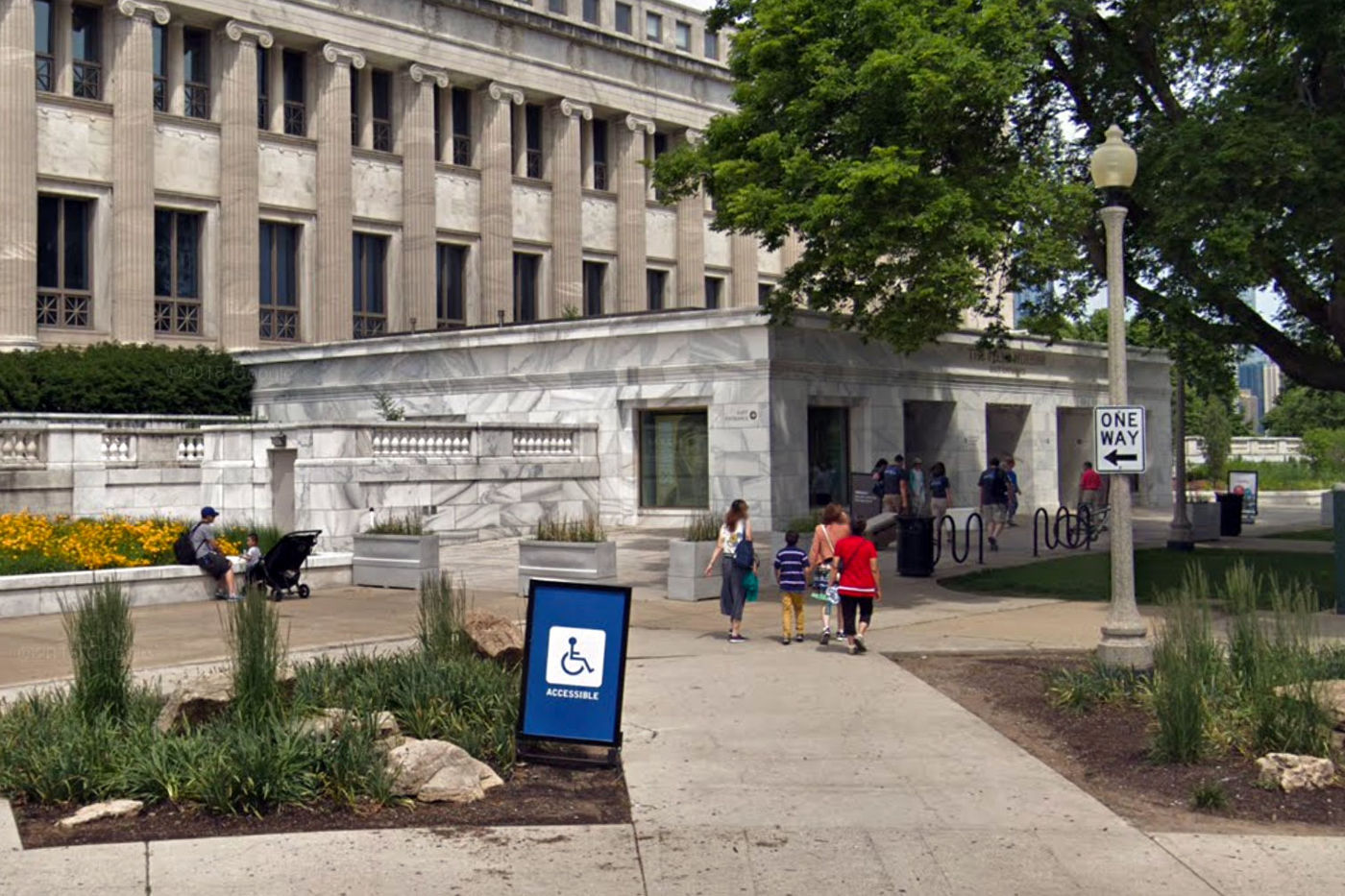 A sidewalk leads to the Field Museum's East entrance, a one-story atrium with gardens next to it. A sign indicates that the entrance is wheelchair accessible.