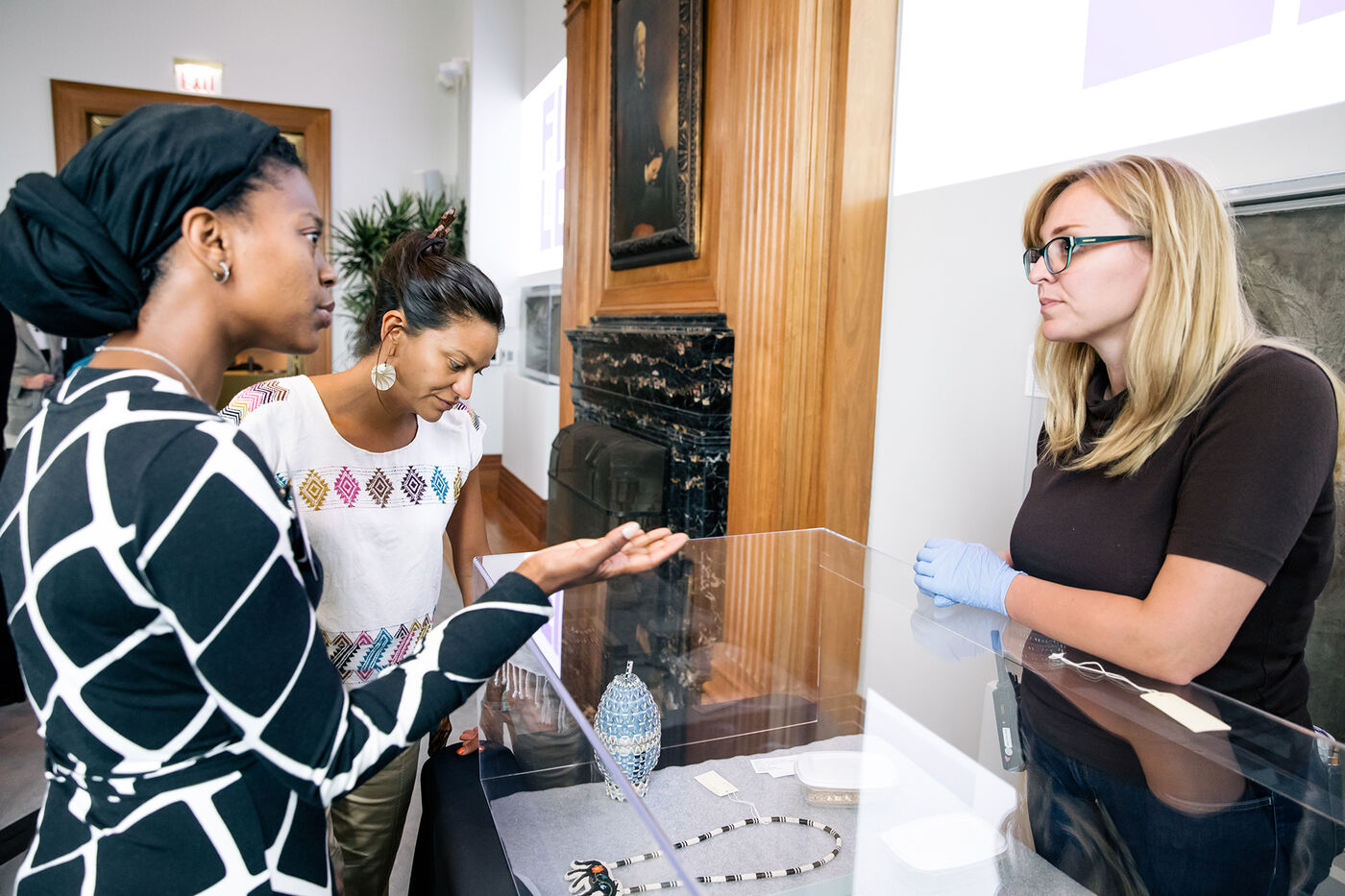 Two attendees and a museum staff member talk over a case filled with objects from the Field Museum's collections