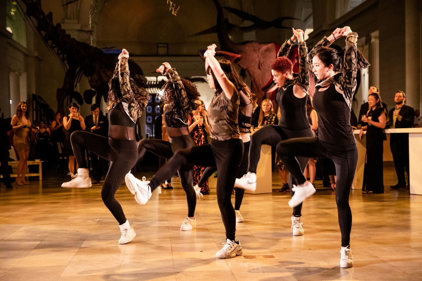 A group of dancers perform in Stanley Field Hall. Guests stand around the dancers, watching and taking photos of the performance.