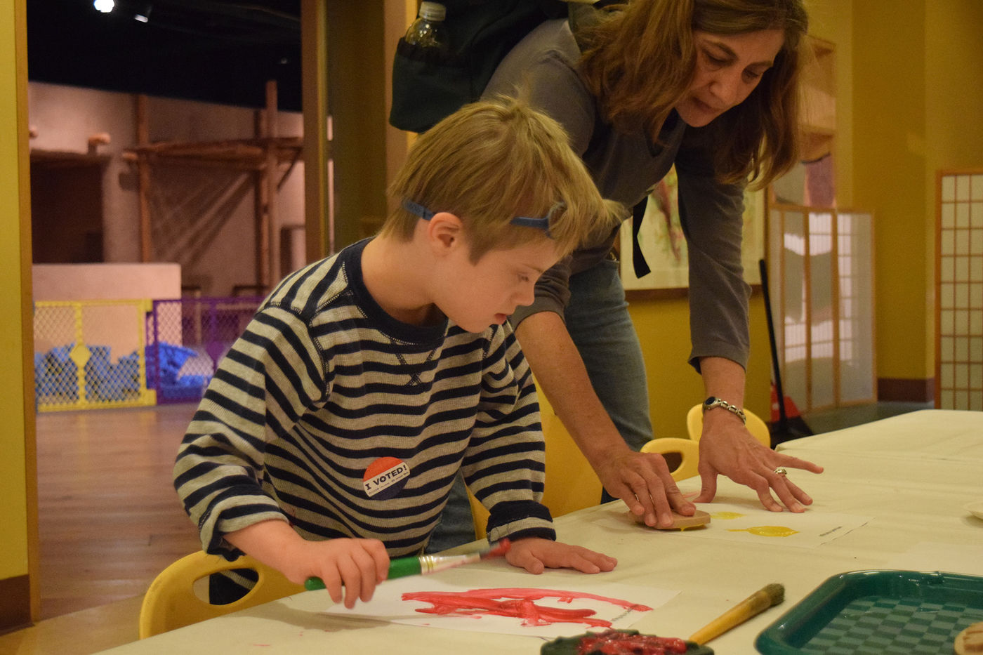 A young visitor paints with his caretaker at a table.