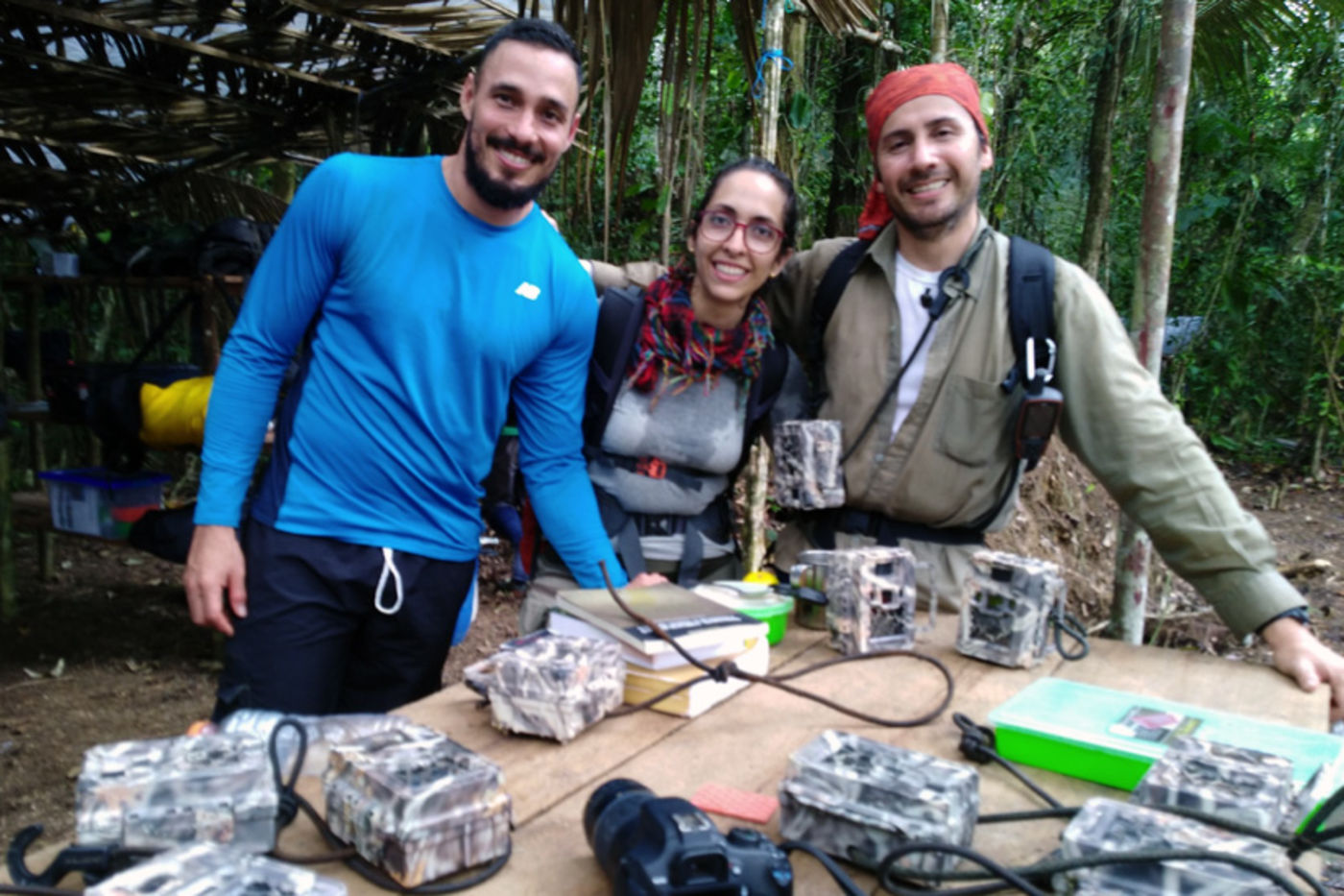 Two men and a woman stand behind a table with several cameras covered in camouflage print. They're at a campsite in the jungle, with lush trees seen in the background.