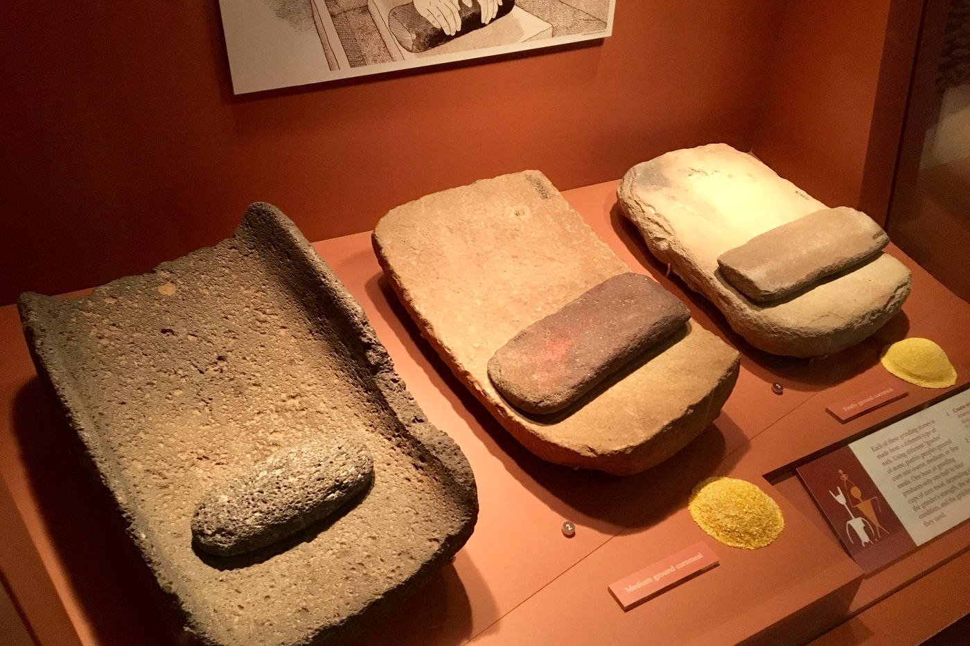 Three rectangular stone slabs with smaller stones to be used as a grinding tool