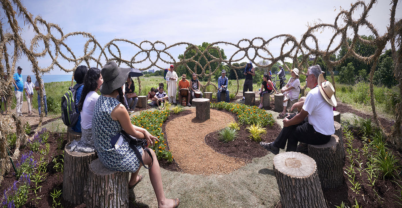 People sitting in a circle around a garden inside a sculptural ring
