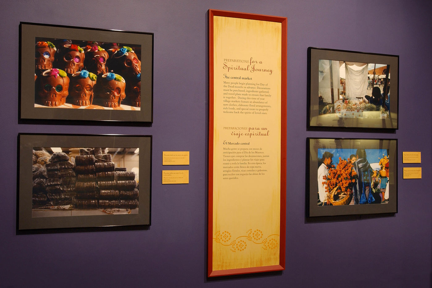 View of A Celebration of Souls exhibition, showing four photographs of different traditions practiced on Dia de los Muertos.