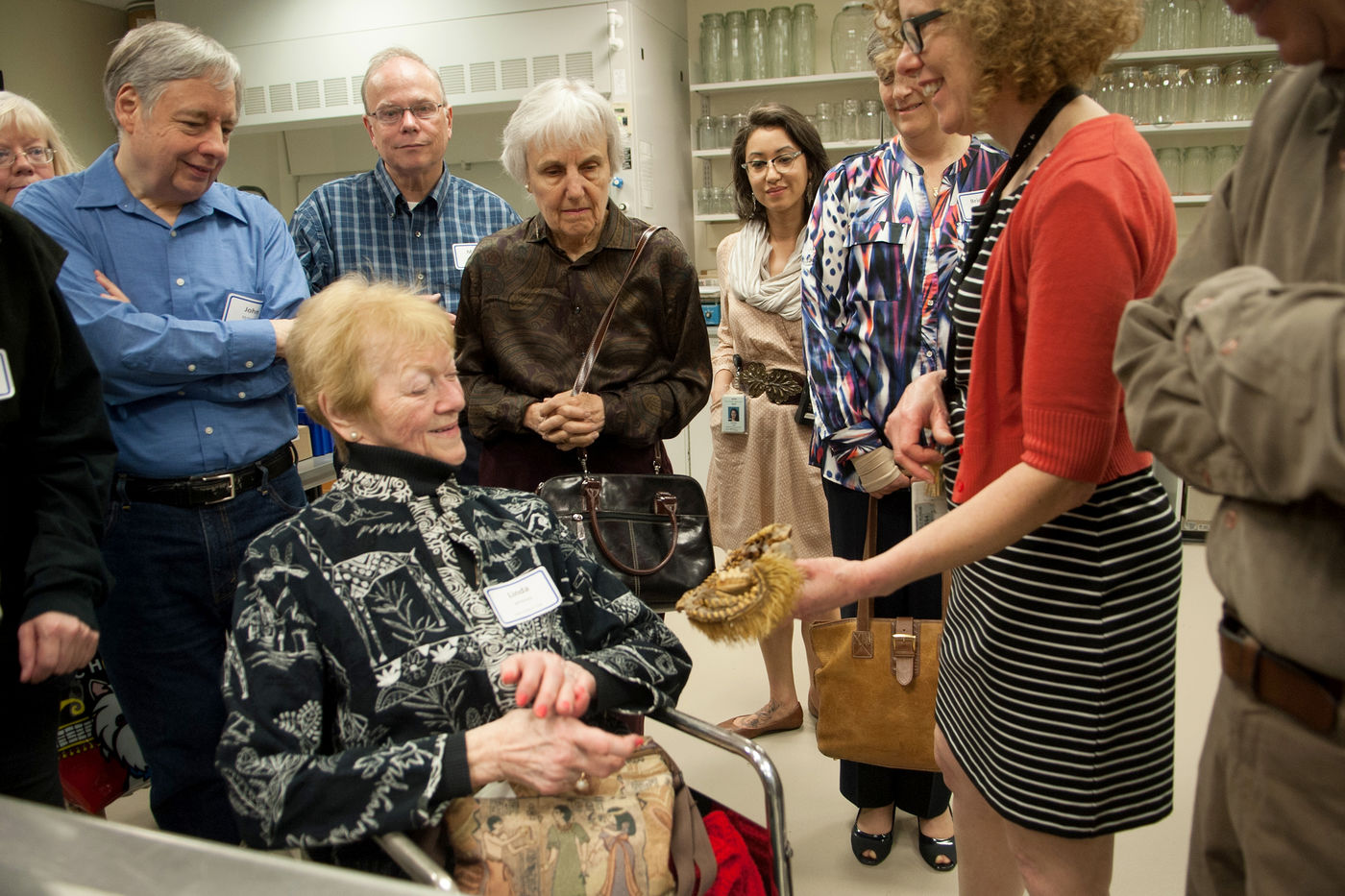 An older woman in a wheelchair smiles as she looks at a specimen held by a staff member. Other adults in the group stand around the pair, looking intently at the specimen. Clear jars are on shelves in the background.