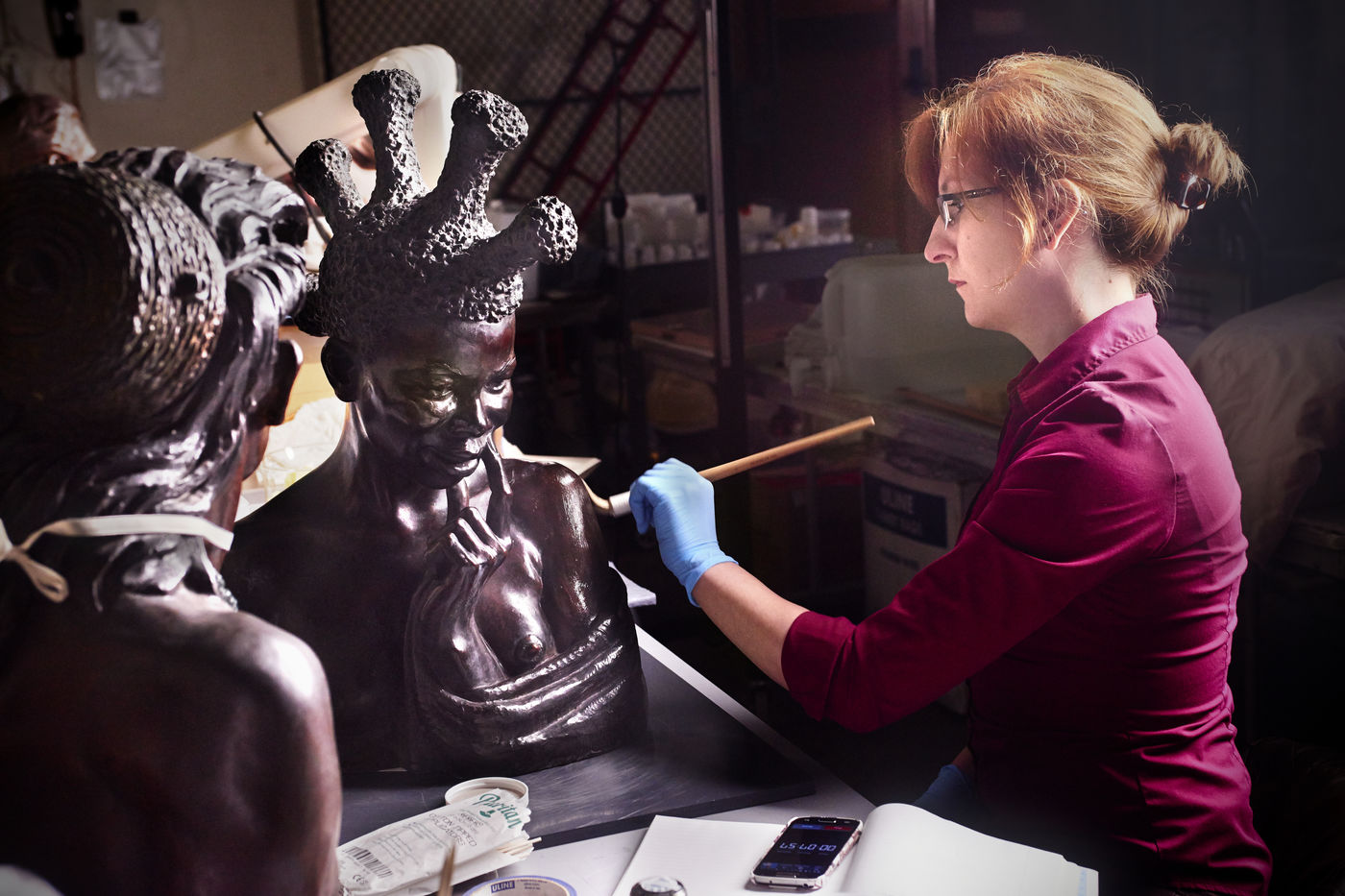 A conservator uses a brush to treat a bronze bust created by Malvina Hoffman. The back of another bust is visible in the foreground.
