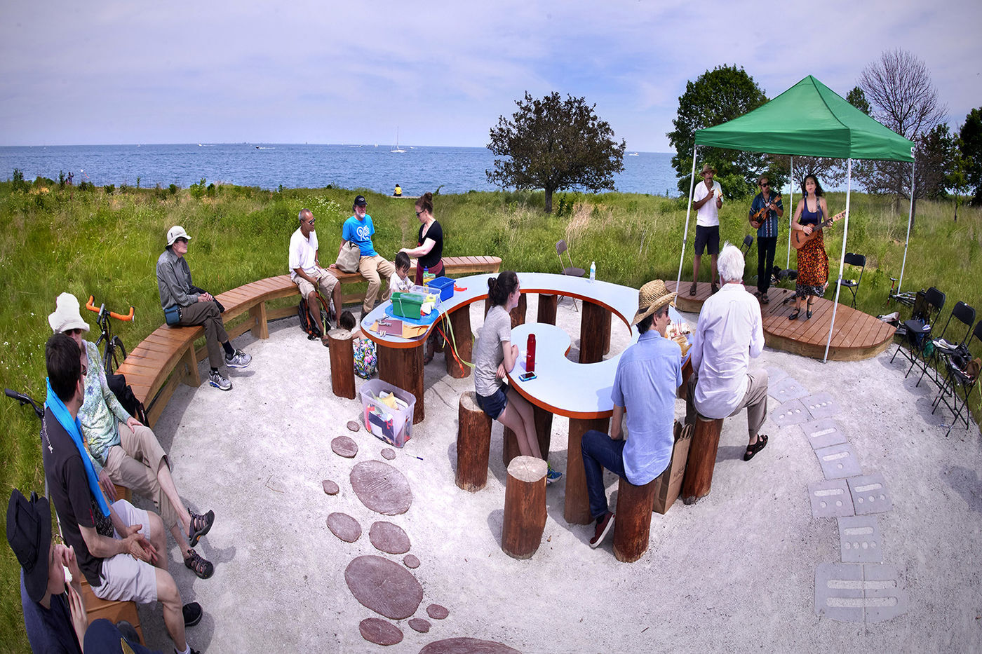A group of people sit around a spiral shaped installation, watching three musicians perform on a small stage with Lake Michigan in the background.