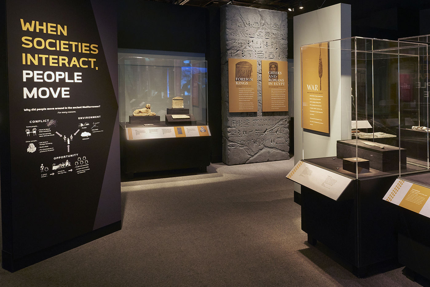 """View of Ancient Mediterranean Cultures in Contact exhibition, showing a large panel reading """"When societies interact, people move."""""""