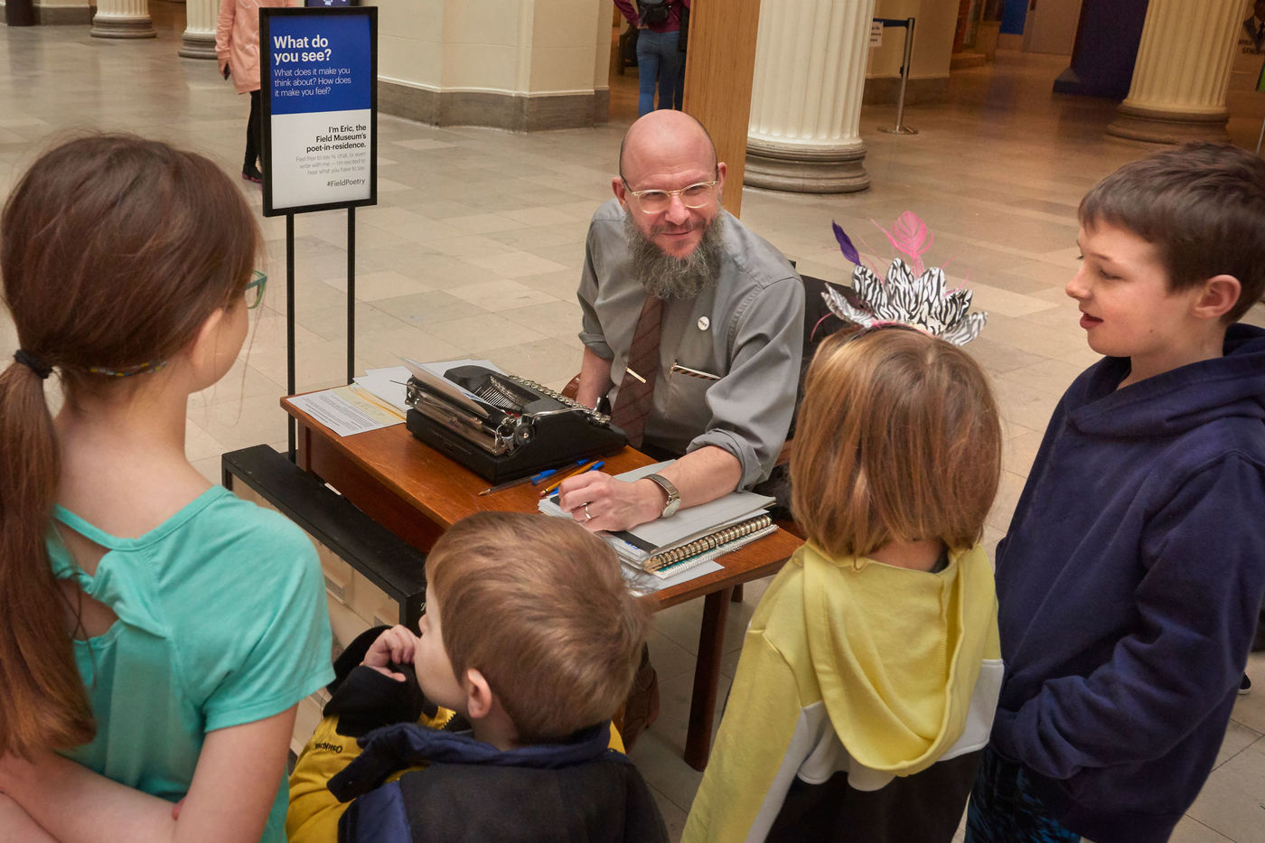"Four small children gather around a desk where a man sits at a typewriter. The desk is situated in the museum's main hall, with columns in the background, and a sign next to the desk reads, ""What do you see?"""