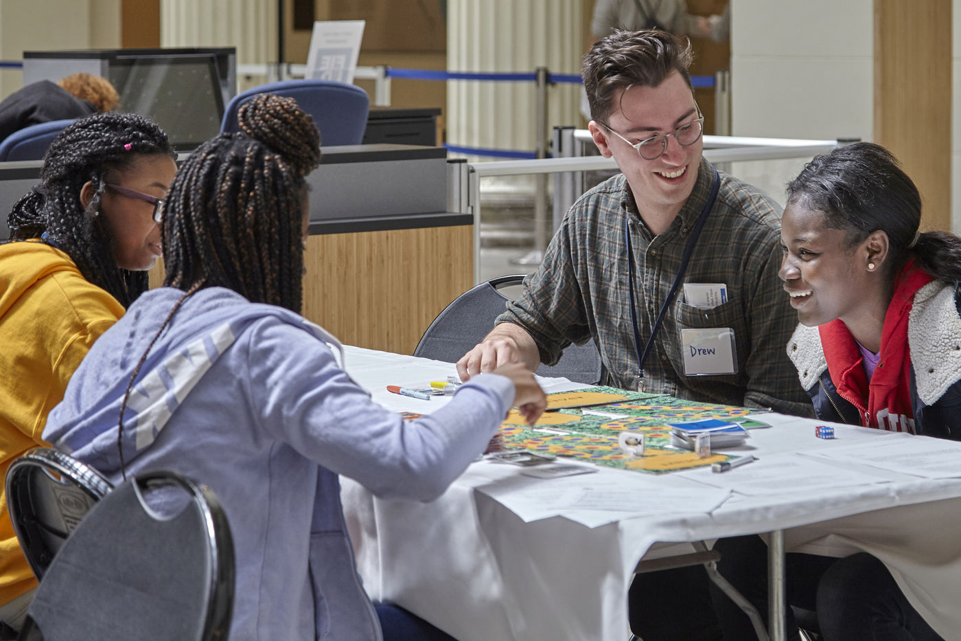 A group of teenagers gather in Stanley Field Hall to play a board game during the Speak Up for Science event.