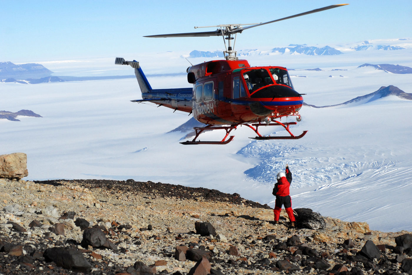 A red helicopter hovers close to the ground, which is rocky in the foreground and an expanse of snow in the background. A person dressed in a red snowsuit and helmet reaches a hand up towards the helicopter to attach a cargo net with fossils.