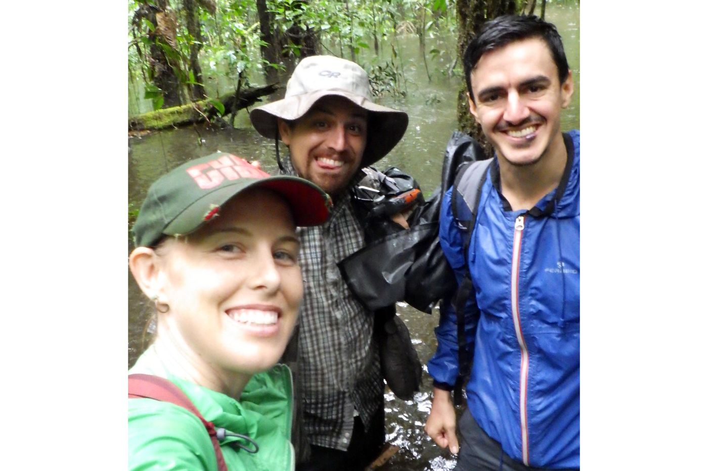 Three people, a woman and two men, take a selfie while standing in a river. They're wearing waterproof camp clothing and are surrounded by trees in the river.