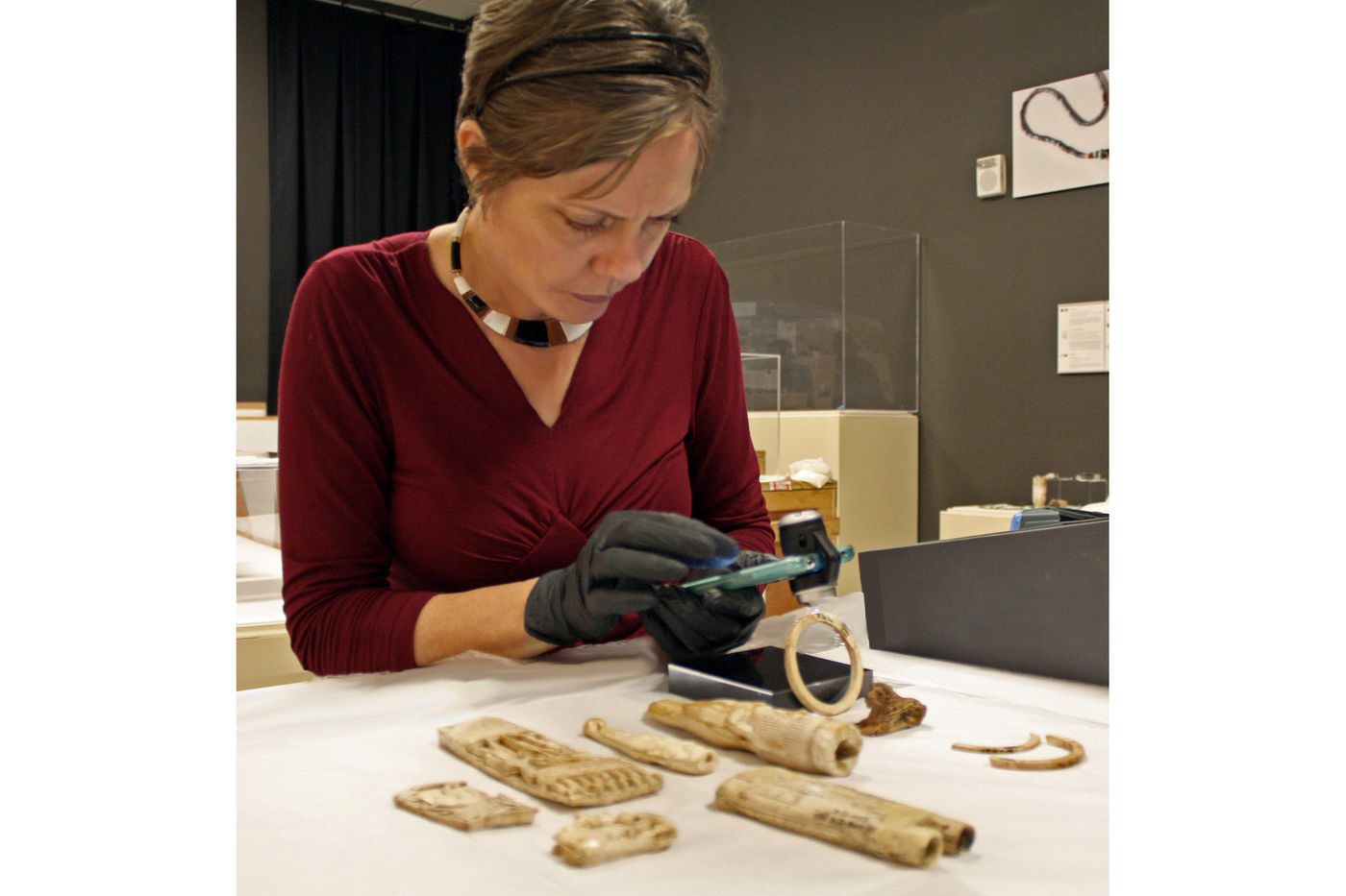 A woman wearing gloves holds a smartphone with a microscope attached to the camera. She holds it over what appears to be an ivory bracelet, peering intently. Several other carved ivory objects rest on the table.