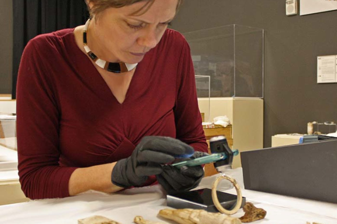 A woman wearing gloves holds a small device over a group of carved ivory objects
