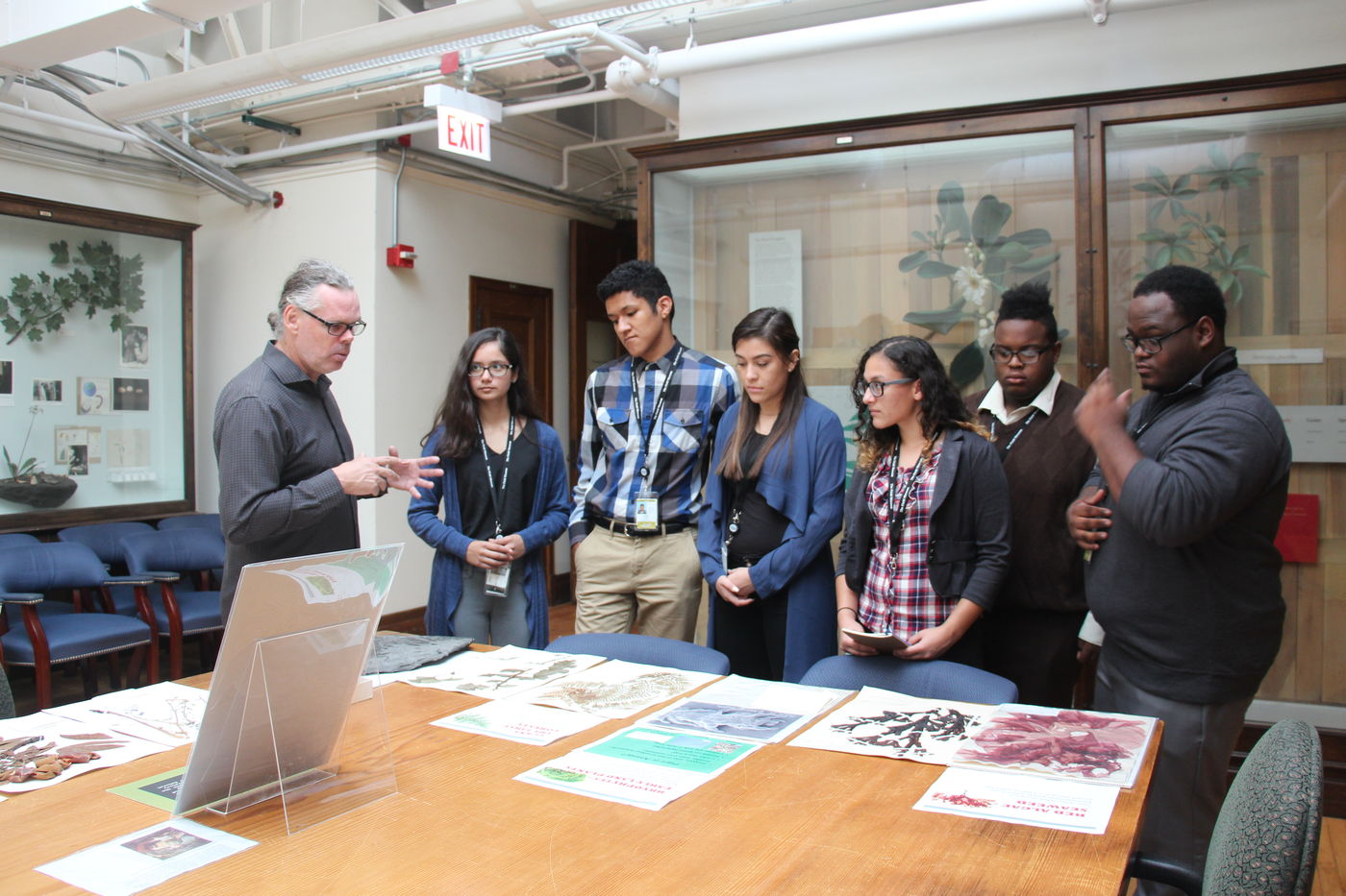 A scientist shares information about the botany collection at the Field Museum with a group of students in a classroom. Images of various plant specimens are laid out on a table as the scientist holds his hands out and lectures. Several cases of wax plant models visible in the background.